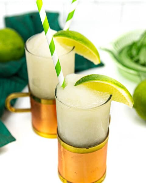 two frozen Moscow mules in a copper and glass mugs with green and white striped paper straws and a wedge of lime on a white background with a green glass citrus squeezer and a green kitchen towel