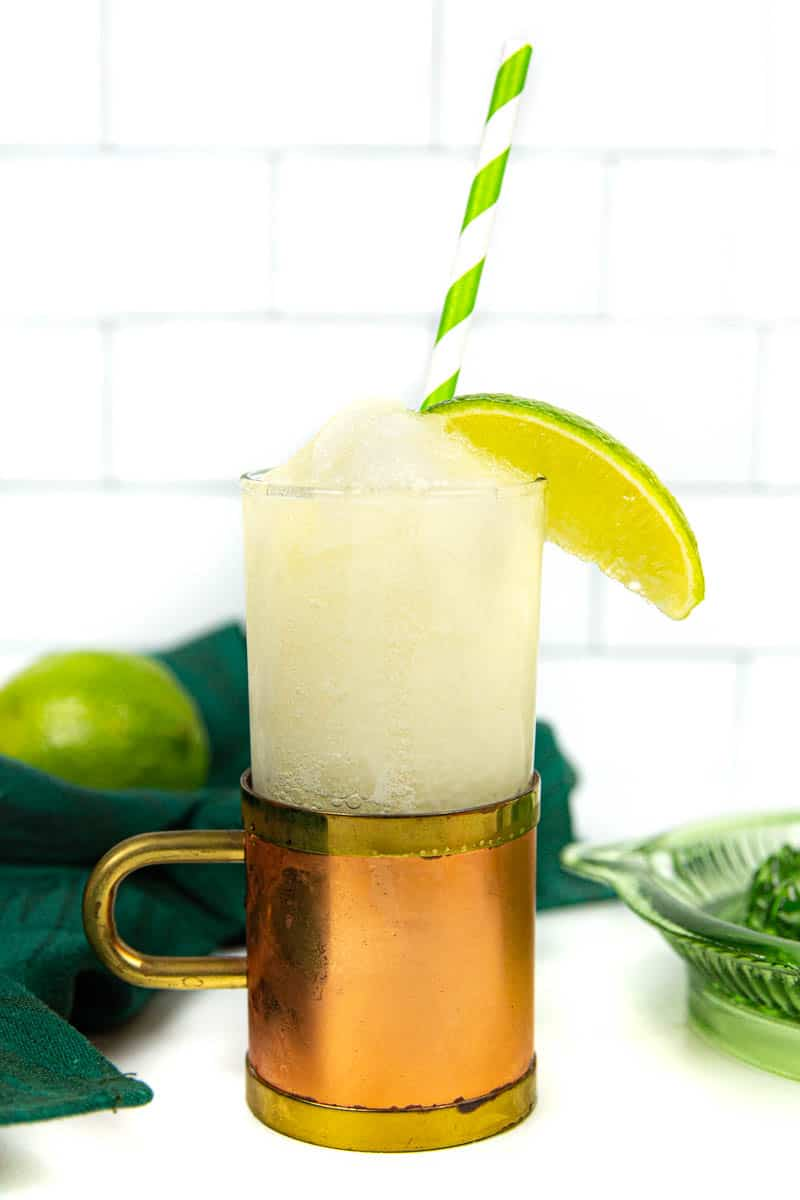 a frozen Moscow mule with a green striped straw and a lime wedge against a white tile background