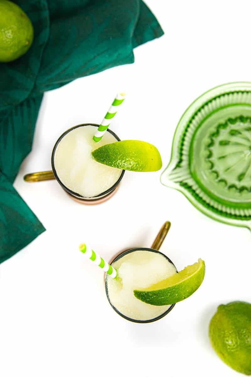top view of two frozen Moscow mules with a green citrus juicer, limes and a dark green kitchen towel