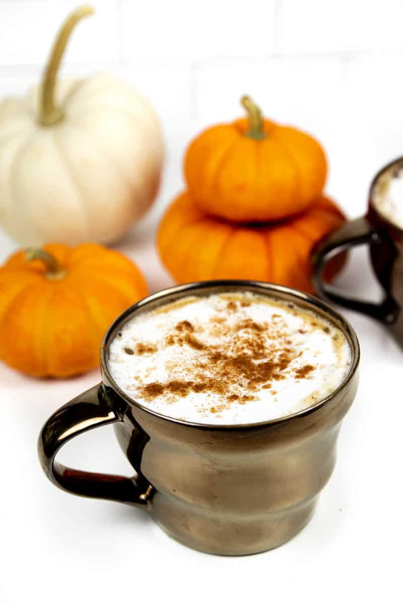an homemade pumpkin spice latte with mini pie pumpkins on a white background