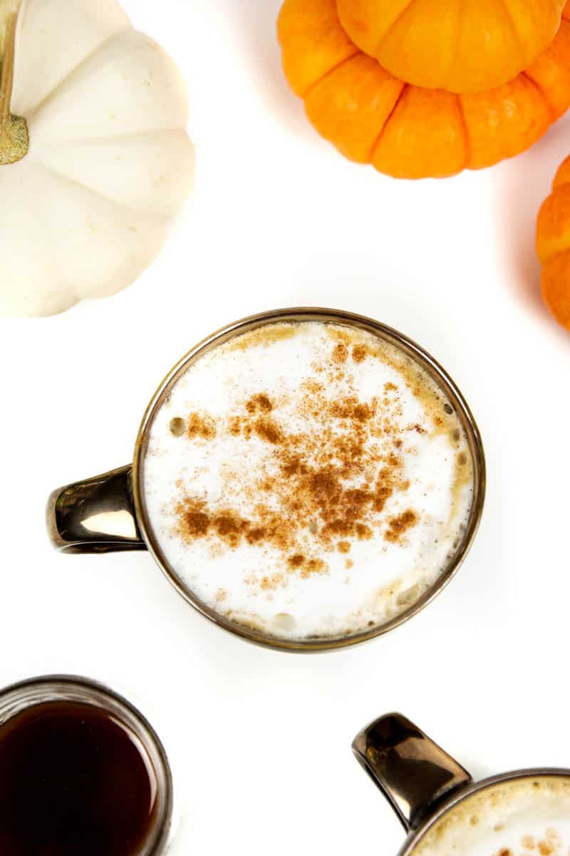 top view of an homemade pumpkin spice latte with a jar of pumpkin spice syrup and mini pumpkins