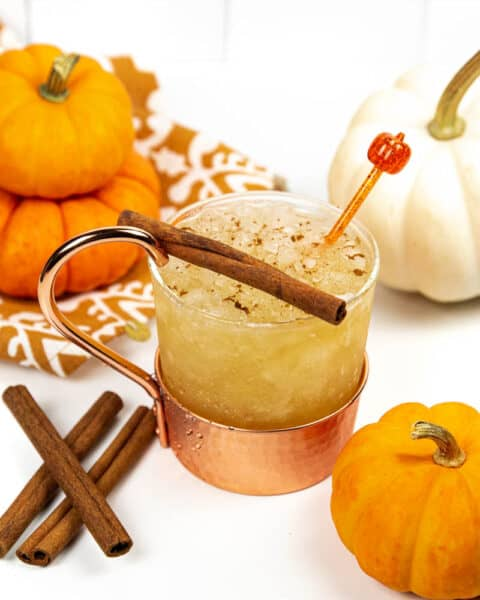 a pumpkin spice mule with pumpkins and an orange and white kitchen towel