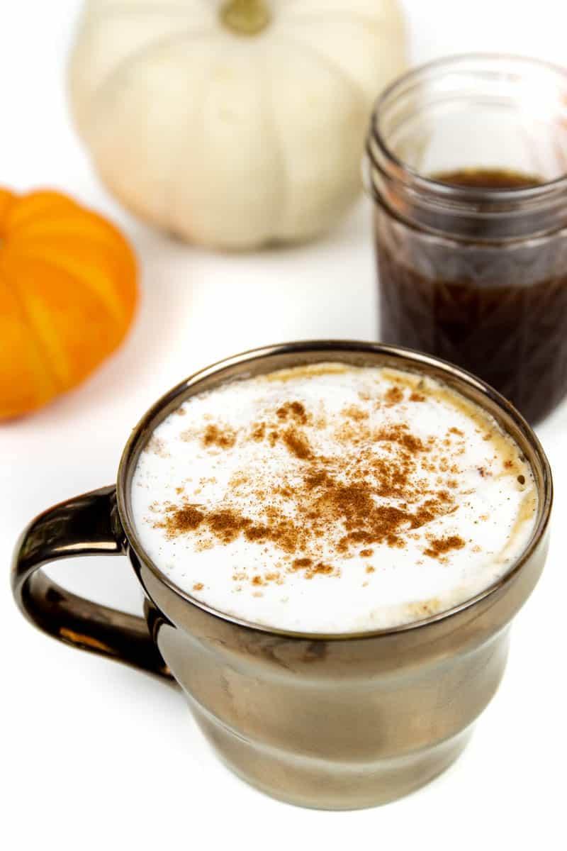 closeup of an homemade pumpkin spice latte with a jar of homemade pumpkin spice syrup on a white background