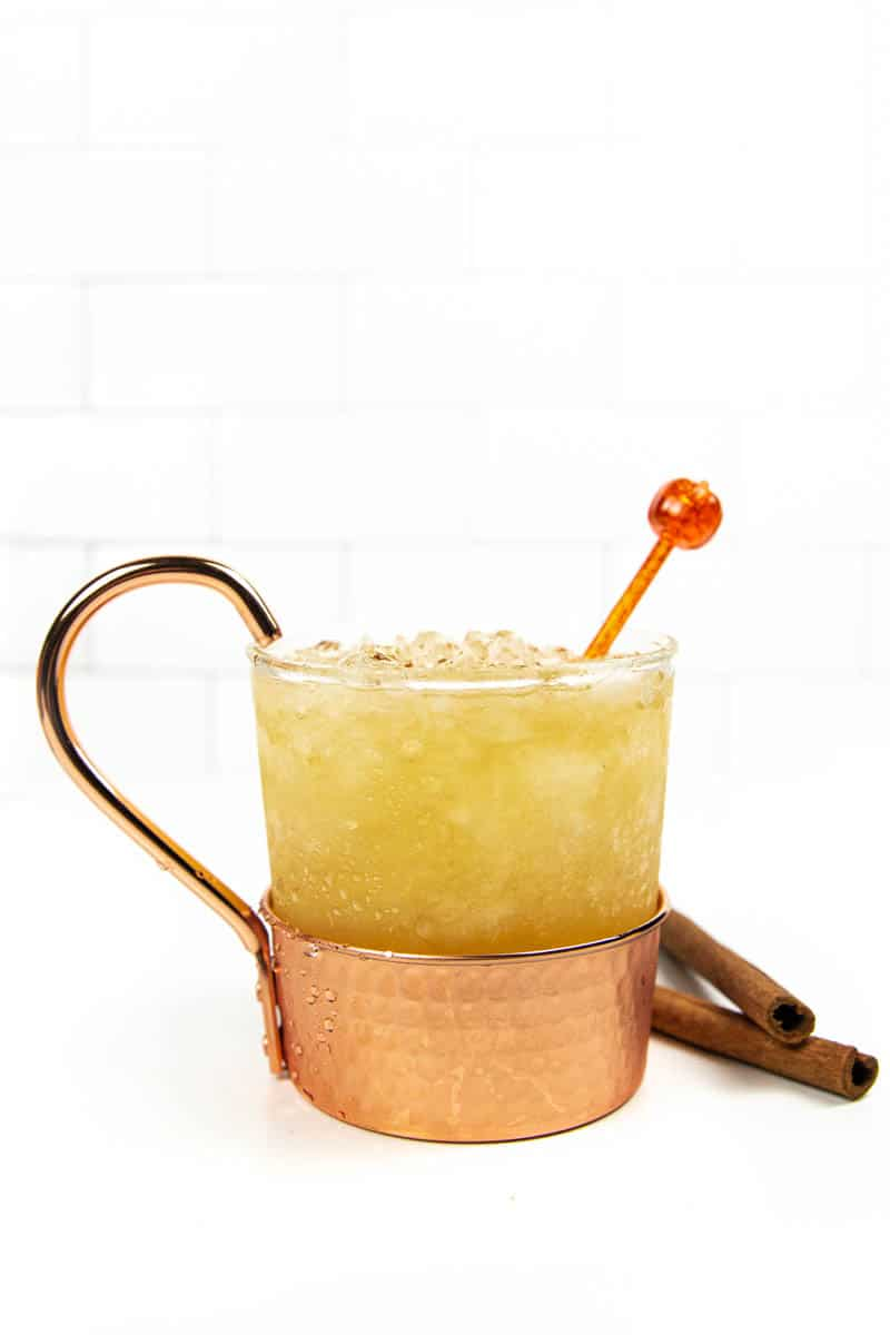 a pumpkin spice mule in a copper mug on a on a white background next to a stack of cinnamon sticks