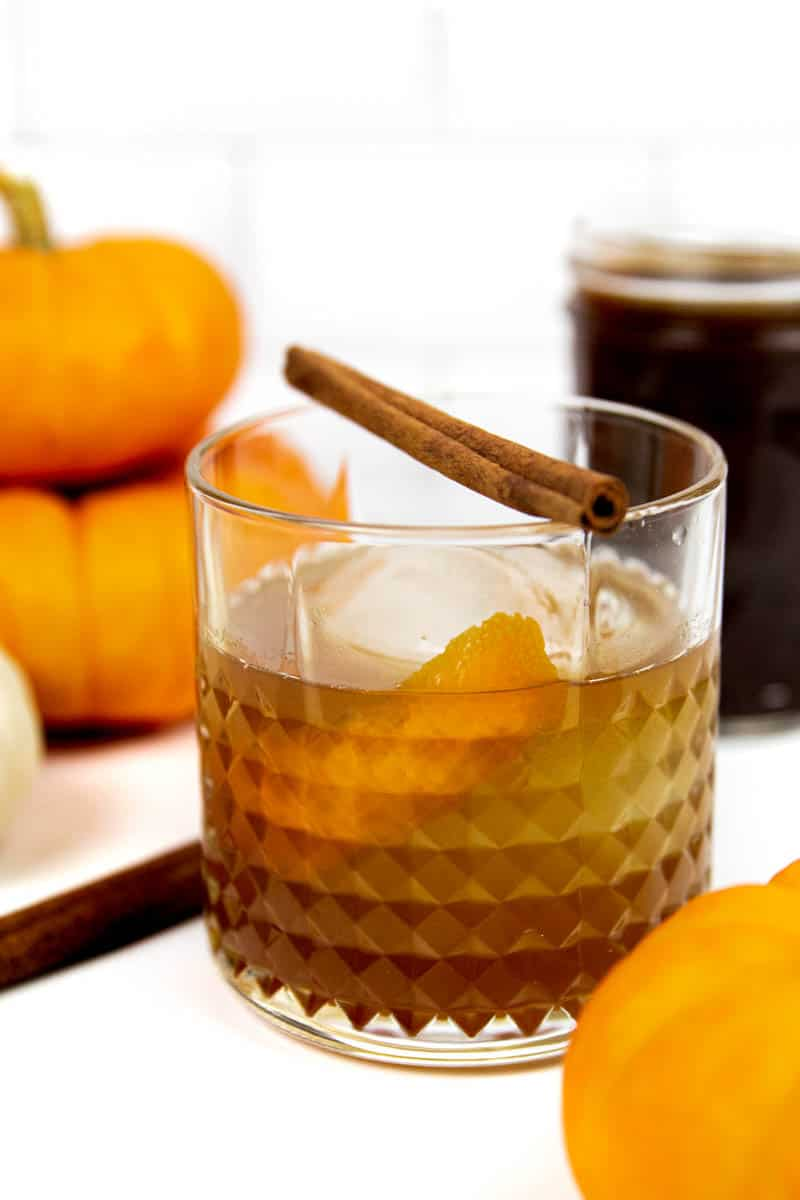 pumpkin spice old-fashioned with pie pumpkins and a jar of pumpkin spice syrup on a white background
