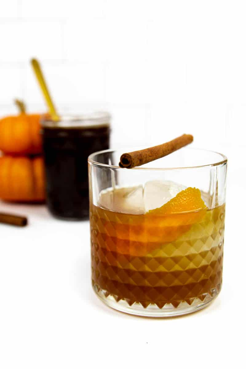 closeup of a pumpkin spice old-fashioned on a white background with a jar of pumpkin spice syrup
