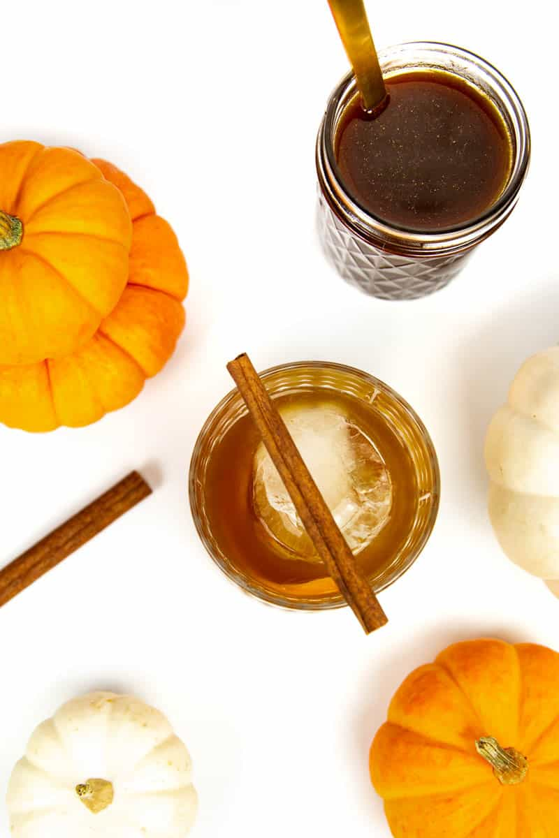 top view of a pumpkin spice old-fashioned with a cinnamon stick on top, next to four pie pumpkins and a jar of pumpkin spice syrup