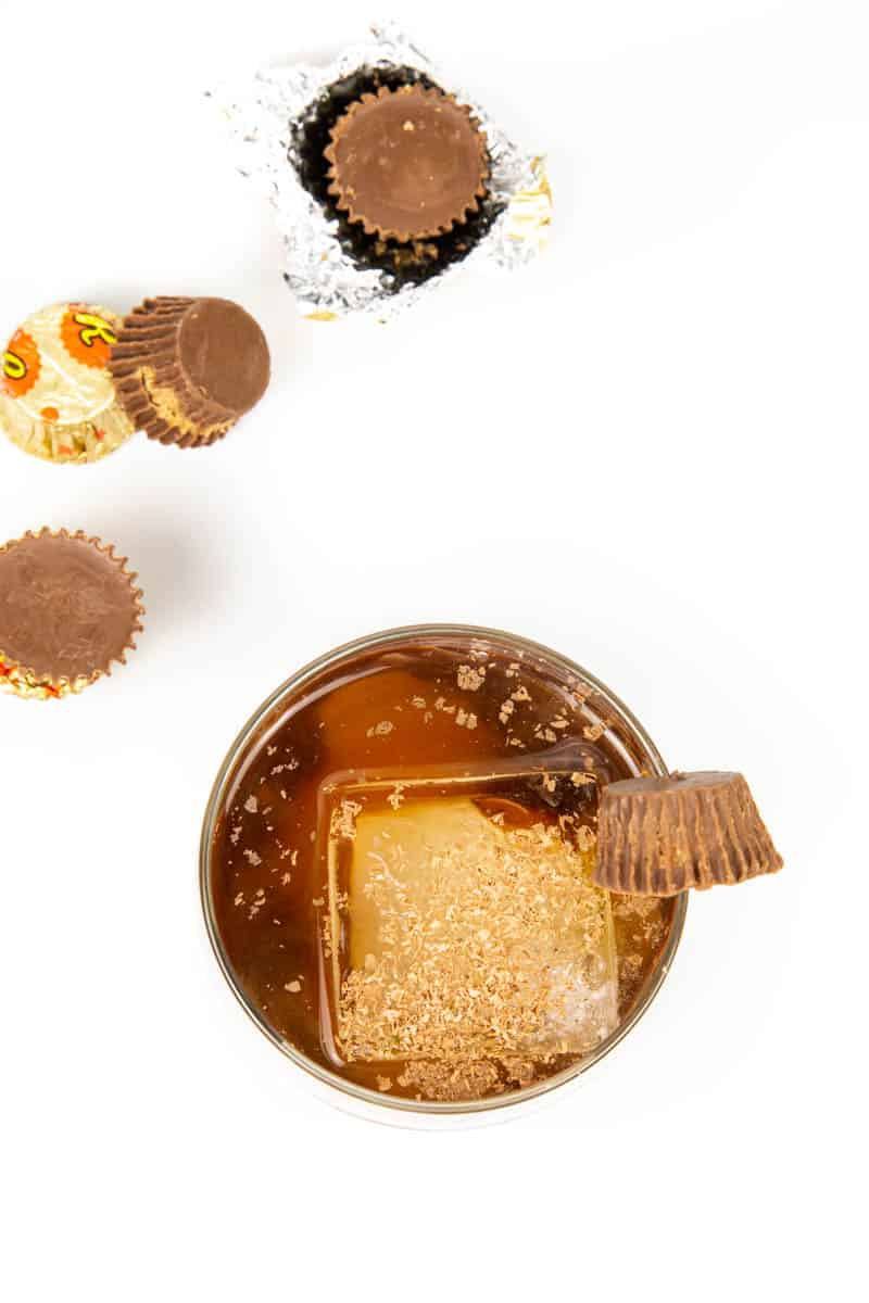 top view of a peanut butter old-fashioned with peanut butter cups on a white background