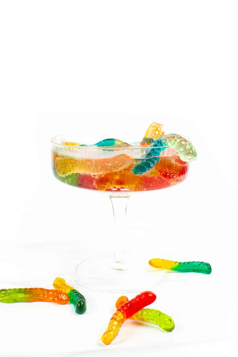 """colorful vodka gummy worms """"crawl"""" out of a coupe glass on a white background"""