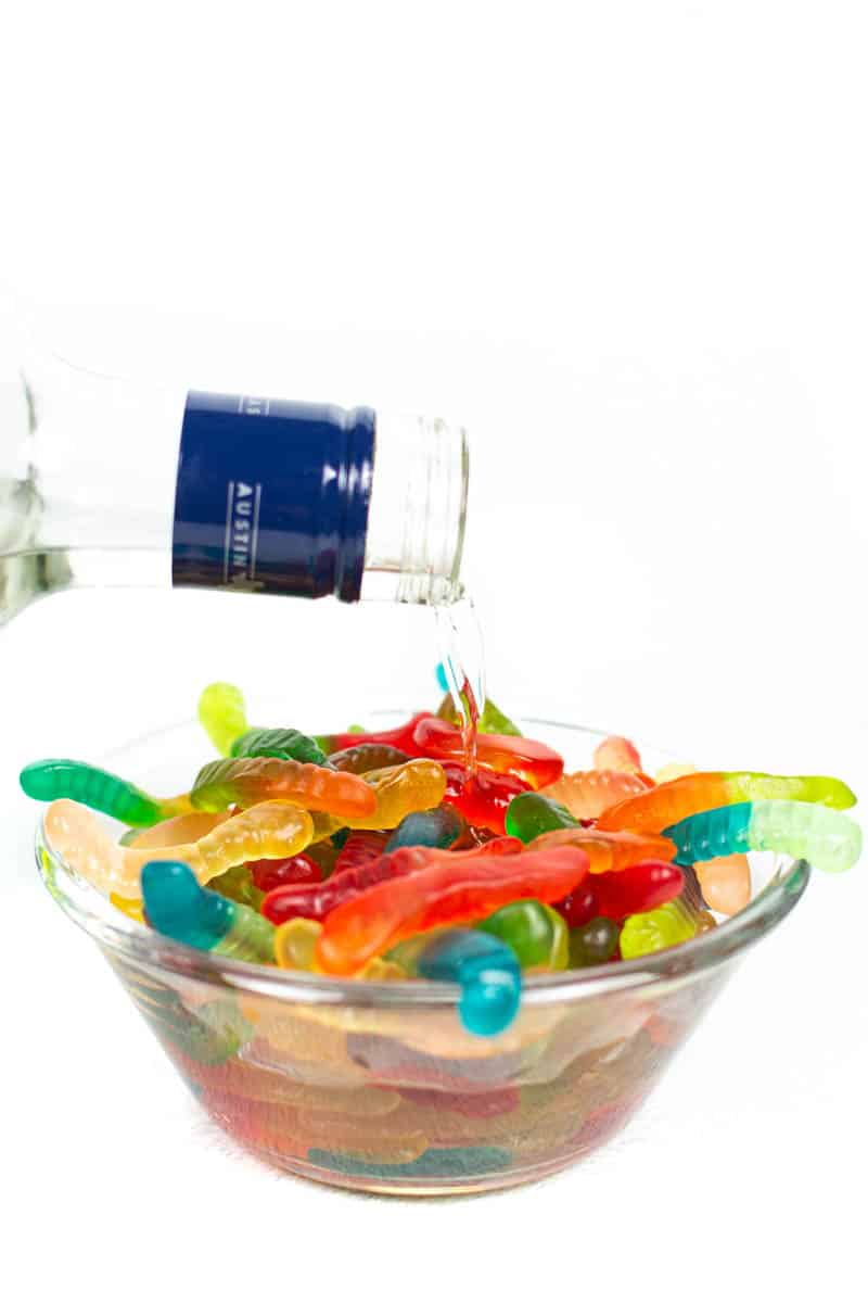 vodka being poured from a glass bottle into a glass bowl filled with gummy worms