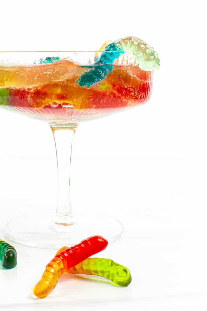 """colorful vodka gummy worms """"crawl"""" out of a coupe glass filled with sprite"""
